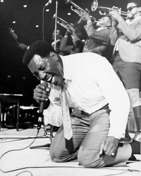 Soul singer Otis Redding passionately gets down on his knees with his horn section behind him as he performs onstage in 1967.